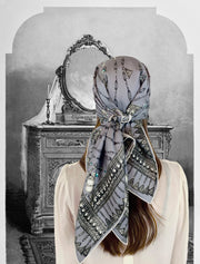 Fantasy Image: Back View of a Classic woman wearing a bespoke Elwyn New York silk scarf on her head with a vintage chain and beaded sautoir print that has intricate, little charm motifs that are strung together in long flowing chains. Woman Standing in front of an ornate Vanity illustration
