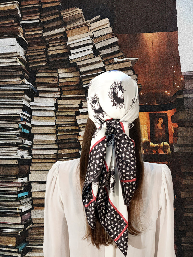 classic female standing in front of a fantastical storefront window piled with books, wearing a luxury, bespoke Elwyn New York silk scarf on her head with black and white, whimsical, polka dot, bird and stars, storybook print