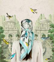 Garden vintage fantasy illustration of a back view of a woman wearing a bespoke Elwyn New York silk scarf around her head with a Charming blue and yellow warbler birds, flying and perched amidst delicate wild flowers. Inspired by nature found in the North East.
