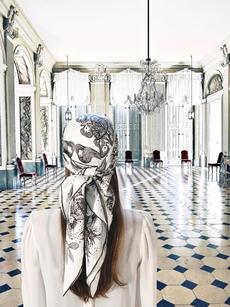 Fantasy photo of the back of a classic female standing in a light filled ballroom, wearing a luxury, bespoke Elwyn New Yorksilk scarf on her head with black and white, art nouveau, whimsical, storybook print