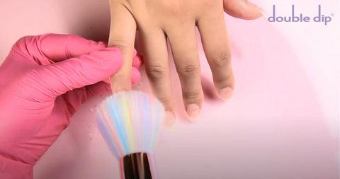 Dust off the excess dip powder with your fluffy nail brush.