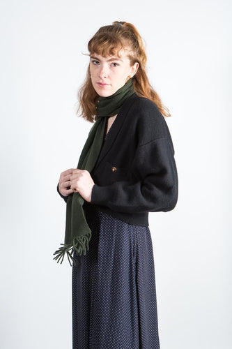 Woman wearing forest green sage wool scarf and polkadot dress and black sweater
