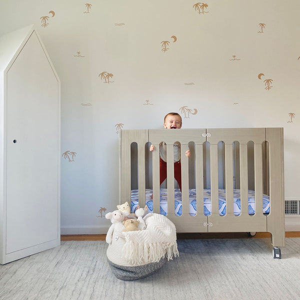 baby standing in beach house grey crib