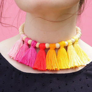 close up of a colorful DIY tassel necklace on a girl