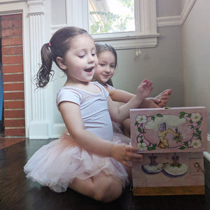 Ballet School Music box with two young girls in tutus | A ballerina is on top in pink with a posey and morning glories around her.  Scenes from the ballet studio are on the side.  Watercolor illustrations and 4 secret corner treasure drawers | Pretty musical gifts for kids from Enchantmints
