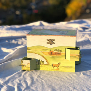 Hideaway horse music box back view in sunshine | Musical treasure boxes and decor for kids from Enchantmints | beautiful gifts for horse lovers with white horse and farmscape in watercolor graphics