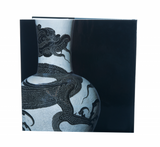 Photo depicts the back of the book, which is void of text and features a close-up image of a white, Chinese vase etched with a black dragon. Background is solid black.