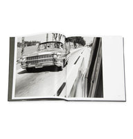 Photo depicts a page from within the catalog, which is a two-page spread of a black and white image of Muhammad Ali behind the wheel of old car, driving down the road with a group of people in his front and back seats. The photo appears to have been taken from another moving car in front of his in the opposite lane, as the window and a portion of the body of the photographer's car can be seen. The street is lined with trees and is adjacent to a body of water.