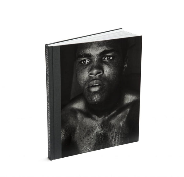 "Photo depicts the front cover of the exhibition catalog for ""Gordon Parks x Muhammad Ali,"" and features a close-up black and white image of Muhammad Ali looking in to the distance and covered in sweat. The spine is a grey fabric, and the title of the book can be seen printed on the spine in a blocky, all-caps black font."