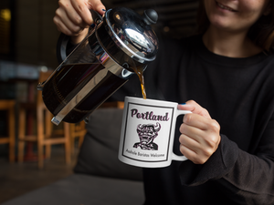 "Woman pouring a cup of coffee from a French press into a white mug with a black and pink demon on it that says ""Portland - Asshole Baristas Welcome"""