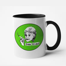 "Load image into Gallery viewer, White mug with a lime green circle and a grunge illustration with Bea Arthur with a blunt that says ""Bea Kind"""