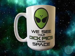 Mug on a space background that has a green alien face image and says in sci-fi font: We See Your Dick Pics From Space.