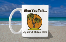 "Load image into Gallery viewer, White mug with a palm tree private island image with the text ""When you talk...My Mind Hides Here.""  Background scene is at the beach."