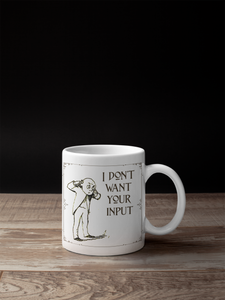 "Mug that says ""I don't want your input"" with a victorian illustration of a guy plugging his ears.  Mug is on a wood table with a black background."