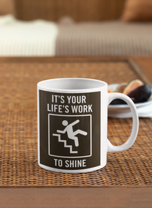 "Mug sitting on a wicker placemat on a table with a plate of figs in the background.  White mug with brown image.  Reminiscent of a traffic sign, has an image of a figure falling down stairs and says ""It's Your Life's Work to Shine."""