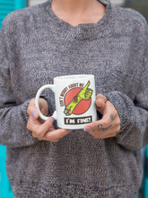 "Load image into Gallery viewer, Woman with cool lavender nail polish and grey sweater holding a mug with an image of a  thumbs up zombie arm that says ""Don't Worry About Me, I'm Fine!"""