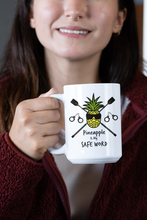 "Load image into Gallery viewer, Young woman holds up a white mug with Image of a Blindfolded pineapple with riding crops and handcuffs.  Mug says ""Pineapple is My Safe Word""."