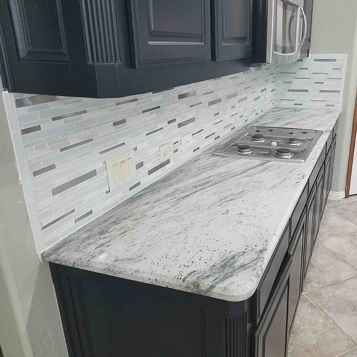dark grey cabinets with light green grey river white granite countertops