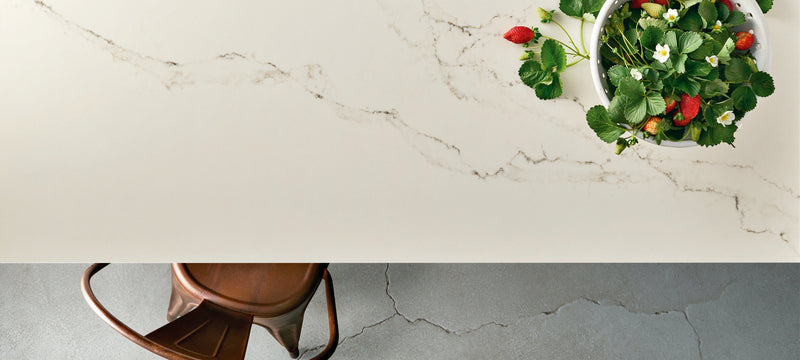 statuario nuvoletti caesarstone table with strawberries and brown chair