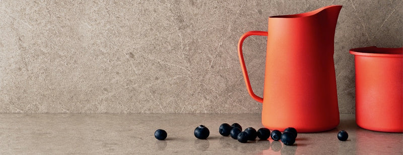red cup with blueberries on the symphony grey countertops with full backsplash
