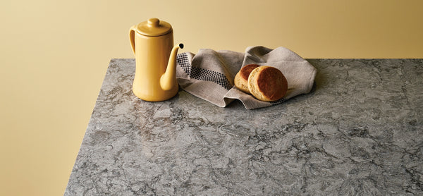 yellow teapot on turbine grey counters with bread and brown towel