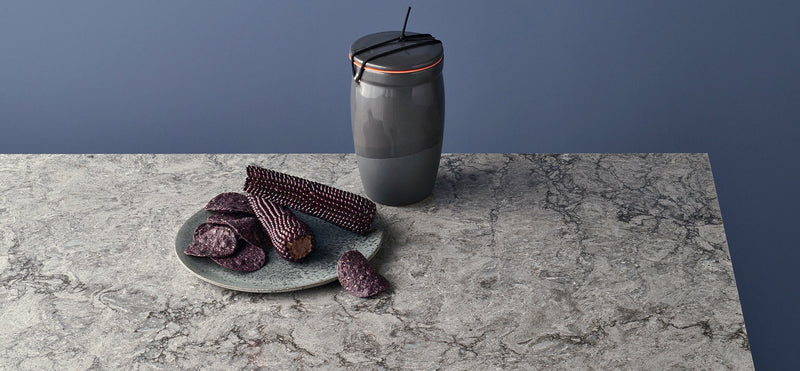 purple corn with grey plate on turbine grey counters with blue background