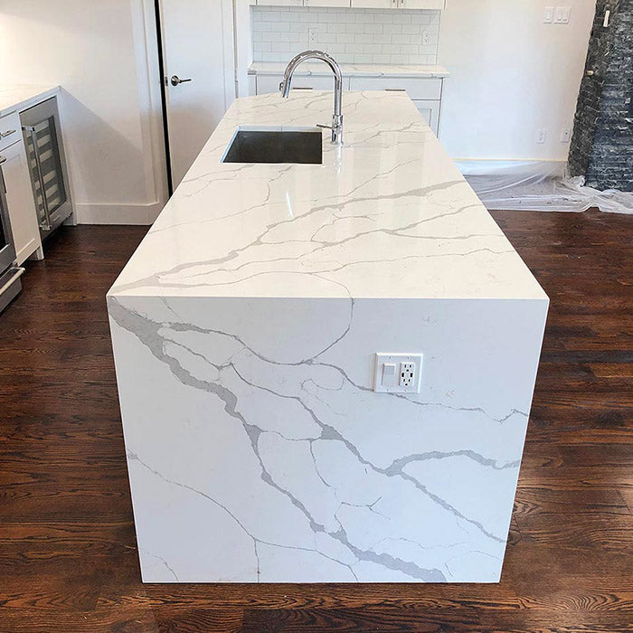 calacatta sponda quartz waterfall kitchen island with stainless steel modern sink