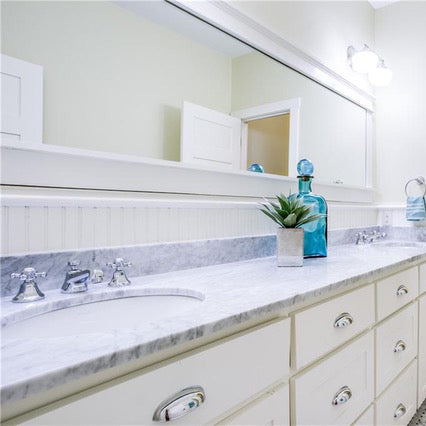 carrara marble bathroom countertops with white oval sinks and white cabinets