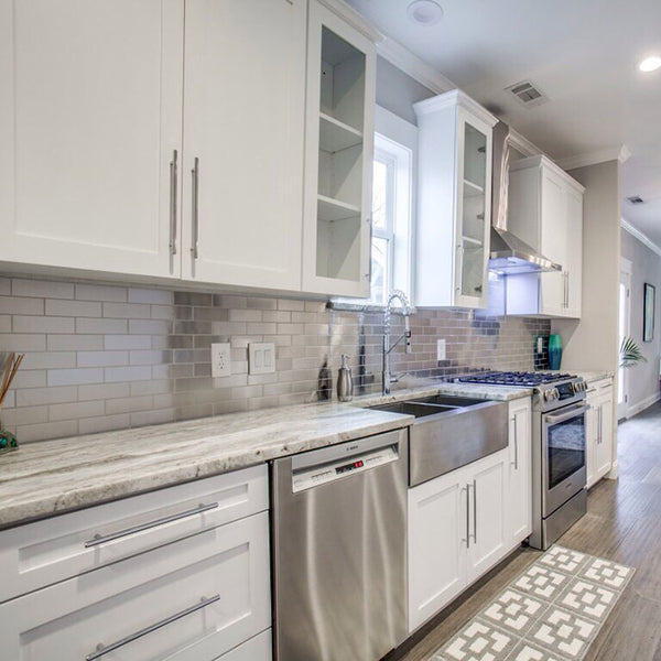 white kitchen cabinets with fantasy brown granite countertops and stainless steel farm sink, aluminum backsplash subway tile