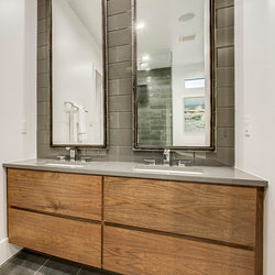 Light brown cabinets with grey quartz vanity tops and white rectangular sinks