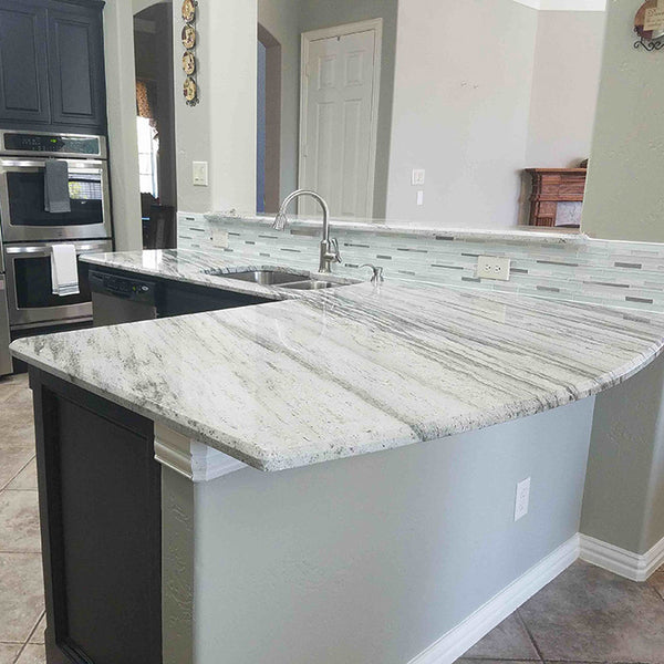 dark grey cabinets with light green grey river white granite countertops and stainless steel sink