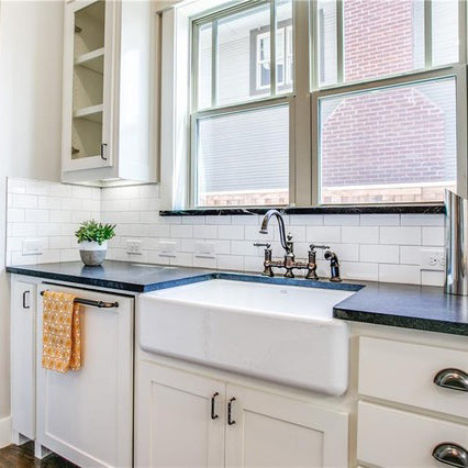 Dark soap stone with white kitchen cabinets, white large cast iron farm sink
