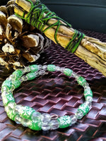 Green and clear scrollwork beaded bracelet