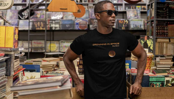 Black man in a record store wearing a black Ryan Koriya Drowning In Space T-Shirt and wearing shades