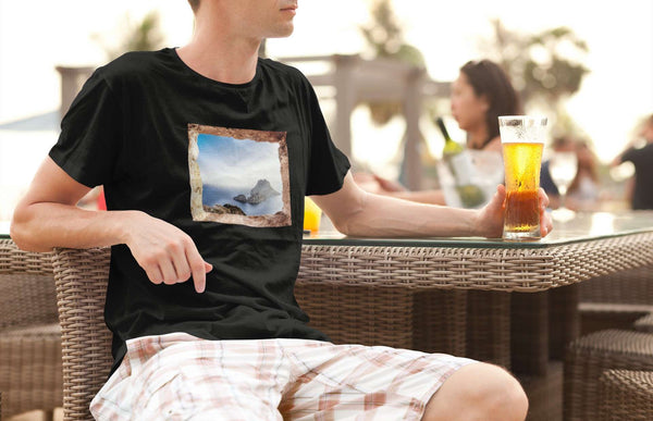 Man drinking a beer in shorts by the beach in an Ibiza t-shirt with Es Vedra design