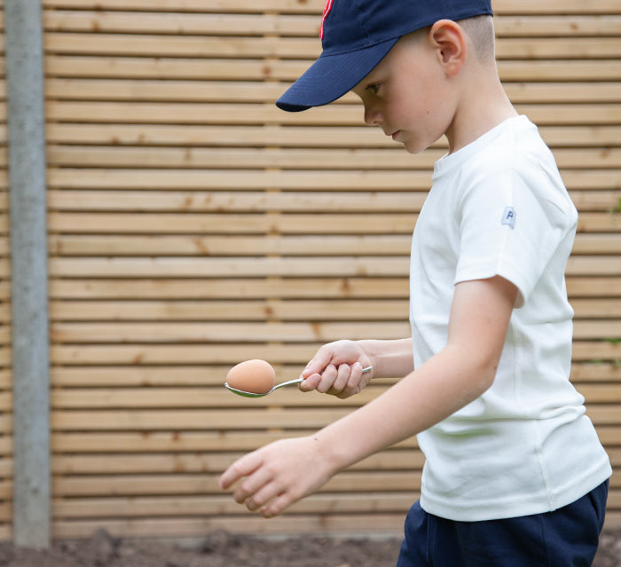 Kid taking part in egg and spoon race for at home sports day