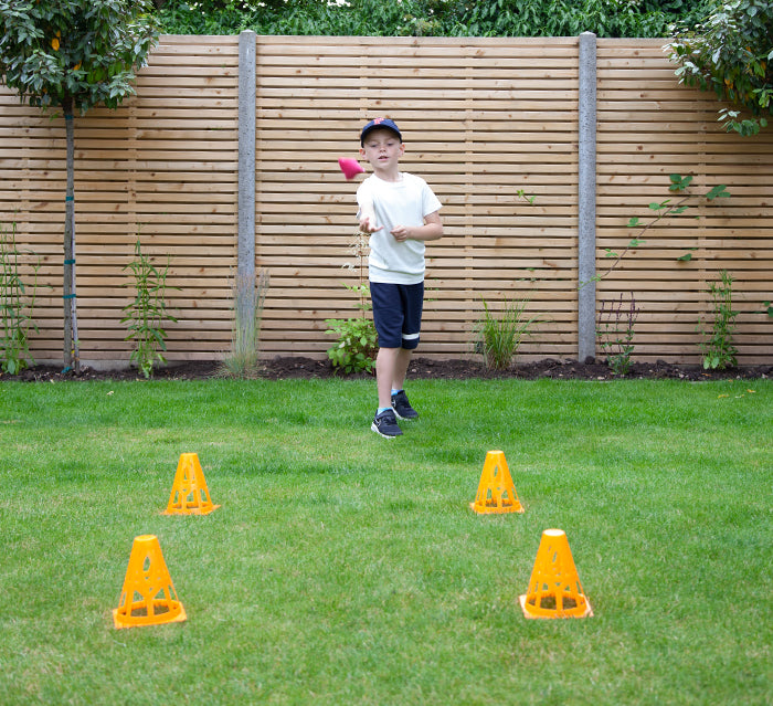 Kid taking part in bean bag throwing for at home sports day