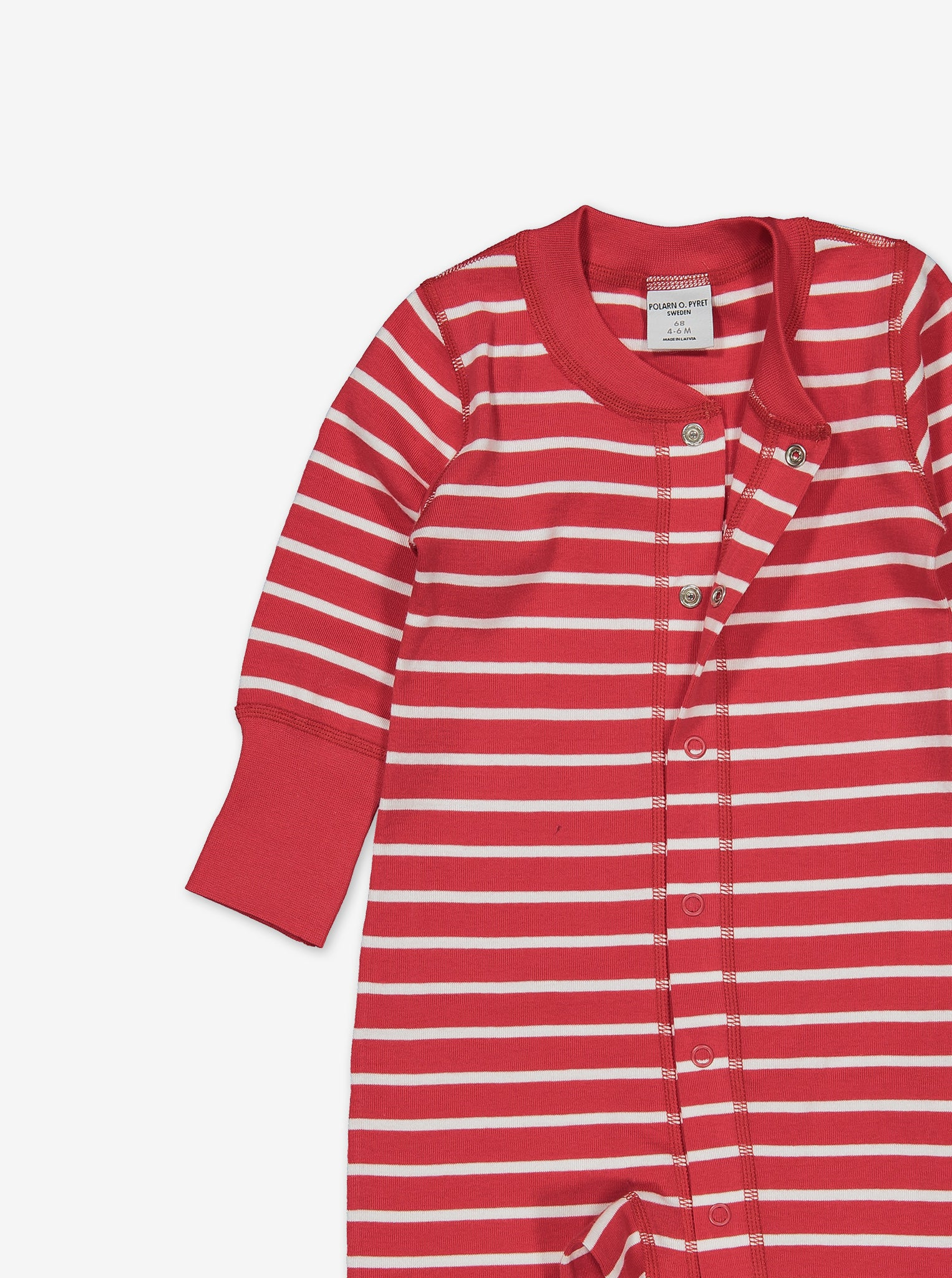 Top chest area of a red and white stripe print baby all-in-one, with the top two poppers unbuttoned for demonstration.