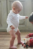 A toddler walking while wearing a white ruffled babygrow that is made from soft, organic cotton material.