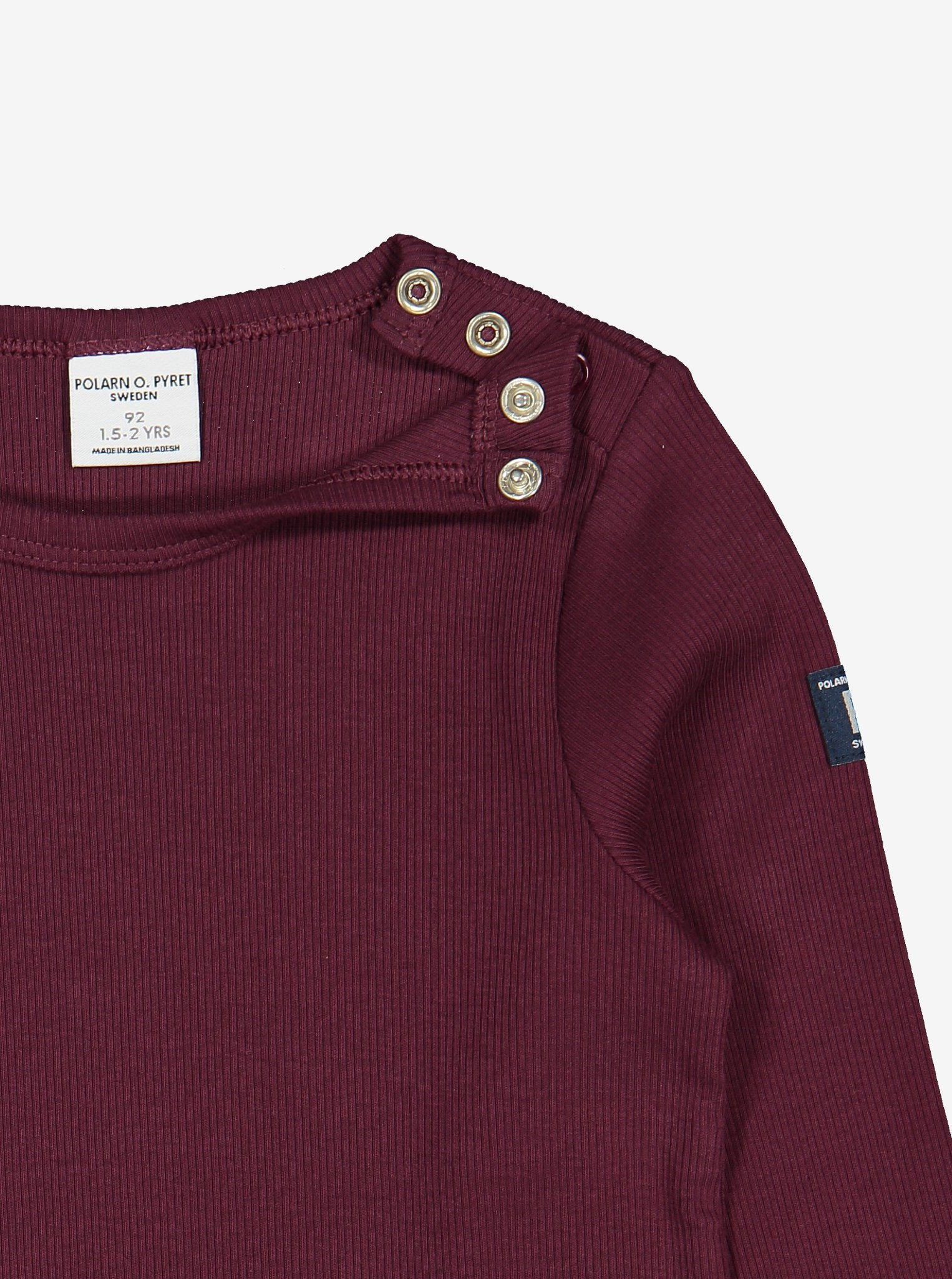 Close up view of kids burgundy red top with helpful poppers on one shoulder for easy dressing. Made in soft organic cotton