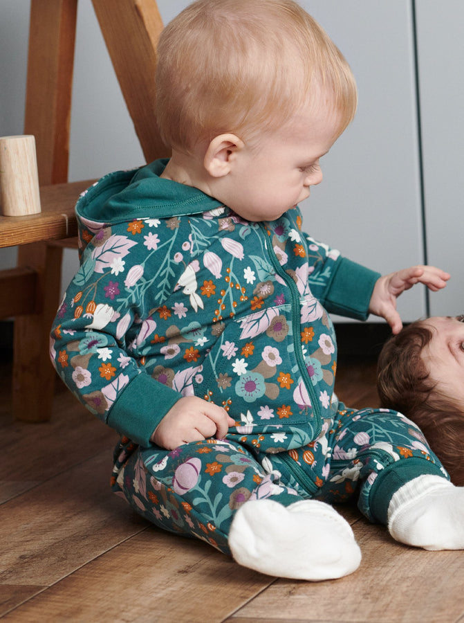 A toddler wearing a Woodland print all-in-one in GOTS organic cotton, paired with plain white cotton socks