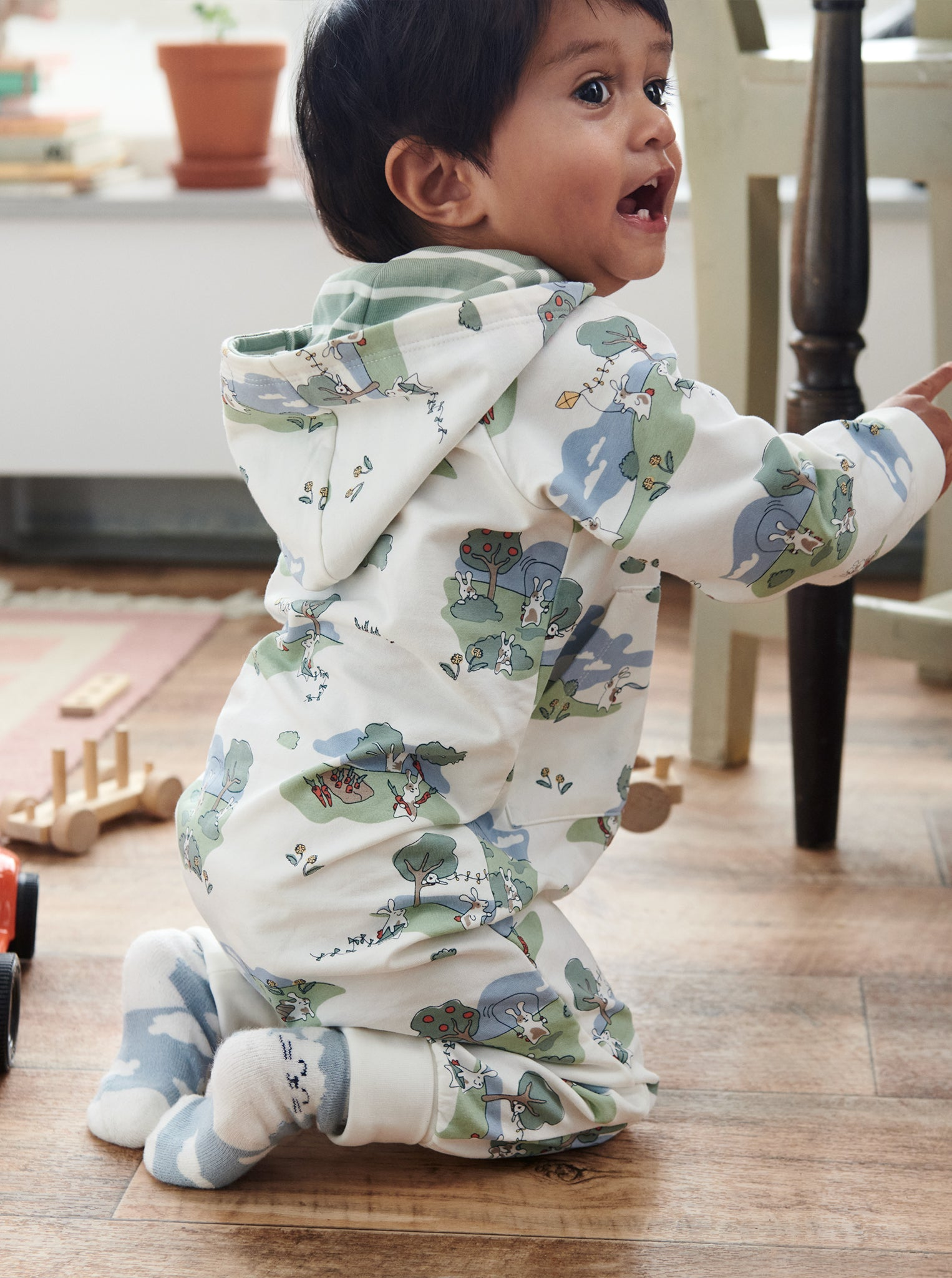 A toddler wearing a bunny print all-in-one in GOTS organic cotton, paired with plain matching cotton socks