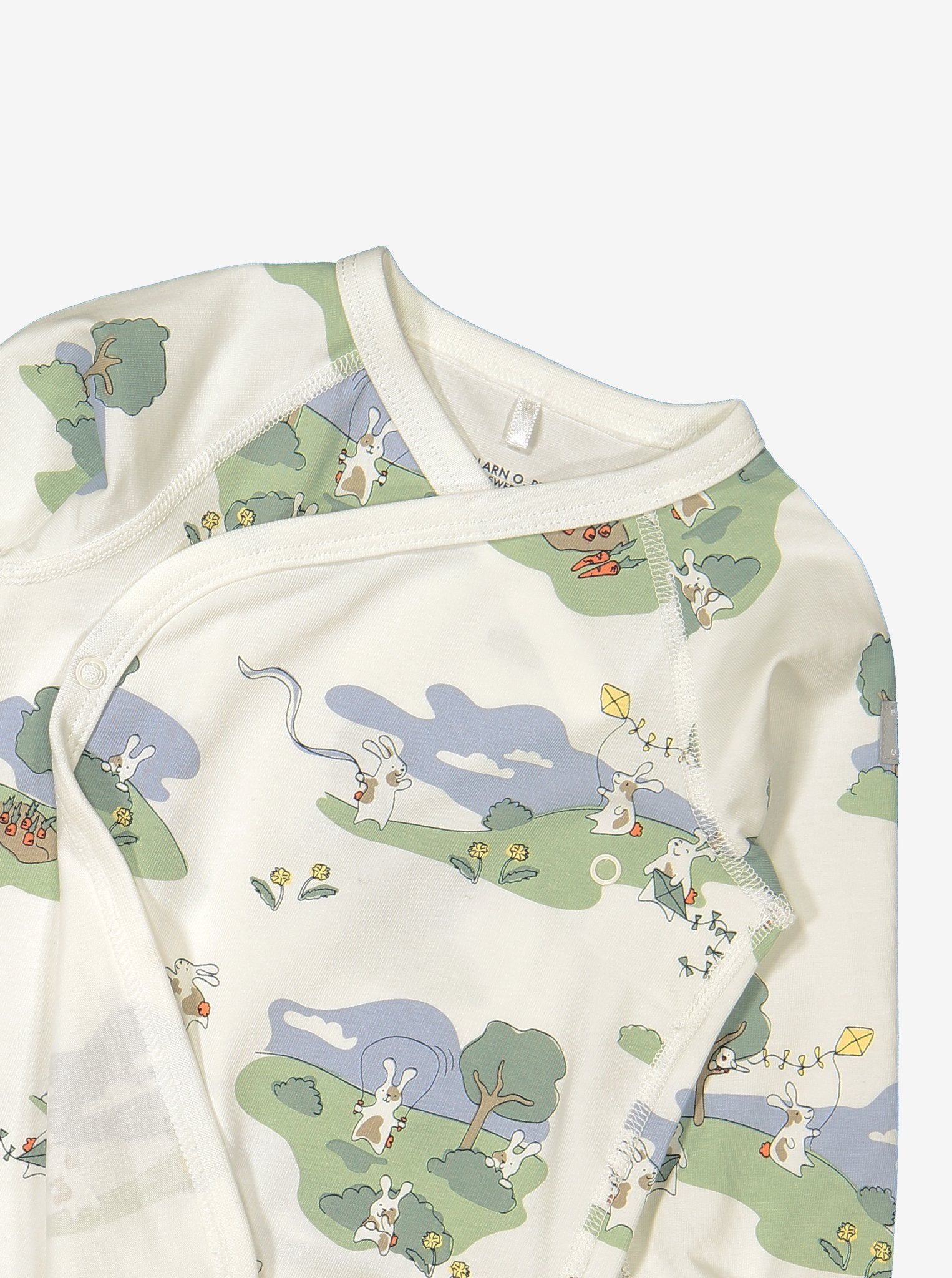 Close up of unisex bunny print wraparound organic cotton newborn babygrow showing quality popper fastening for easy dressing