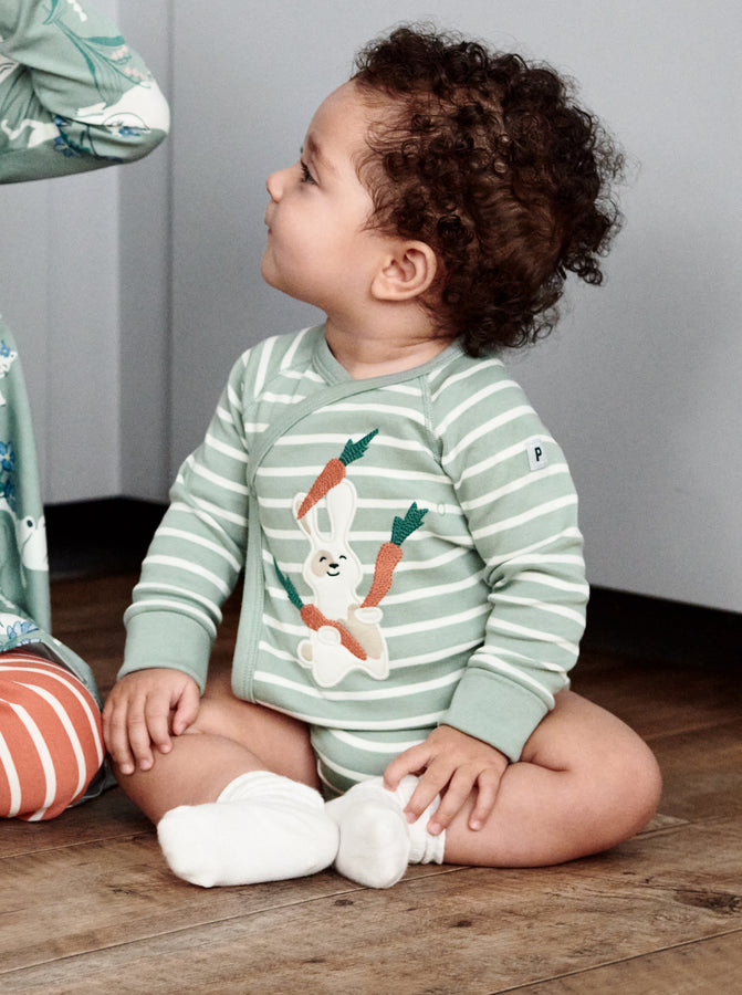 A toddler wearing a green and white striped cotton long sleeve babygrow with fun bunny eating carrots applique, paired with white organic cotton socks