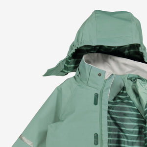 A closeup shot of a green, kids waterproof shell jacket with detachable hood, made of fabric and 100% polyester lining.