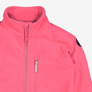 Close up shot of pink, kids waterproof fleece jacket made of breathable fabric, with reflector zip and front pocket.