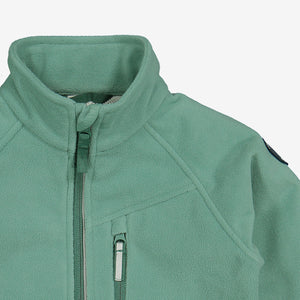 Close up shot of green, kids waterproof fleece jacket made of soft and flexible fabric, comes with reflector on zips and a front pocket.