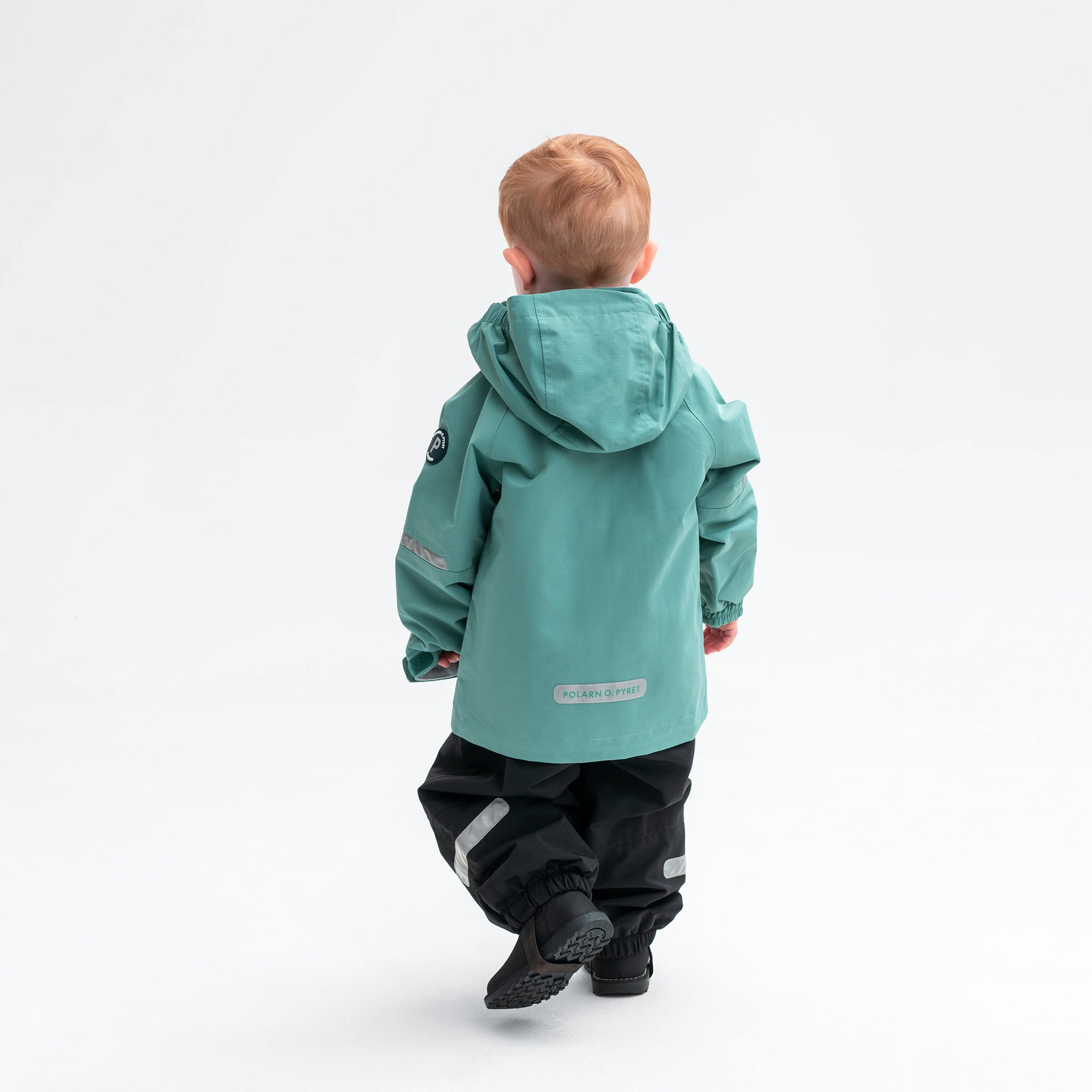 A little boy wearing a green kids waterproof shell jacket with hood, made from eco-friendly water repellent technology.