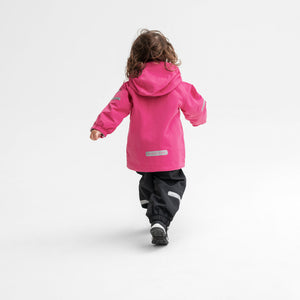 Back view of a girl wearing a pink, kids waterproof jacket paired with black, kids waterproof trousers, made of shell fabric.