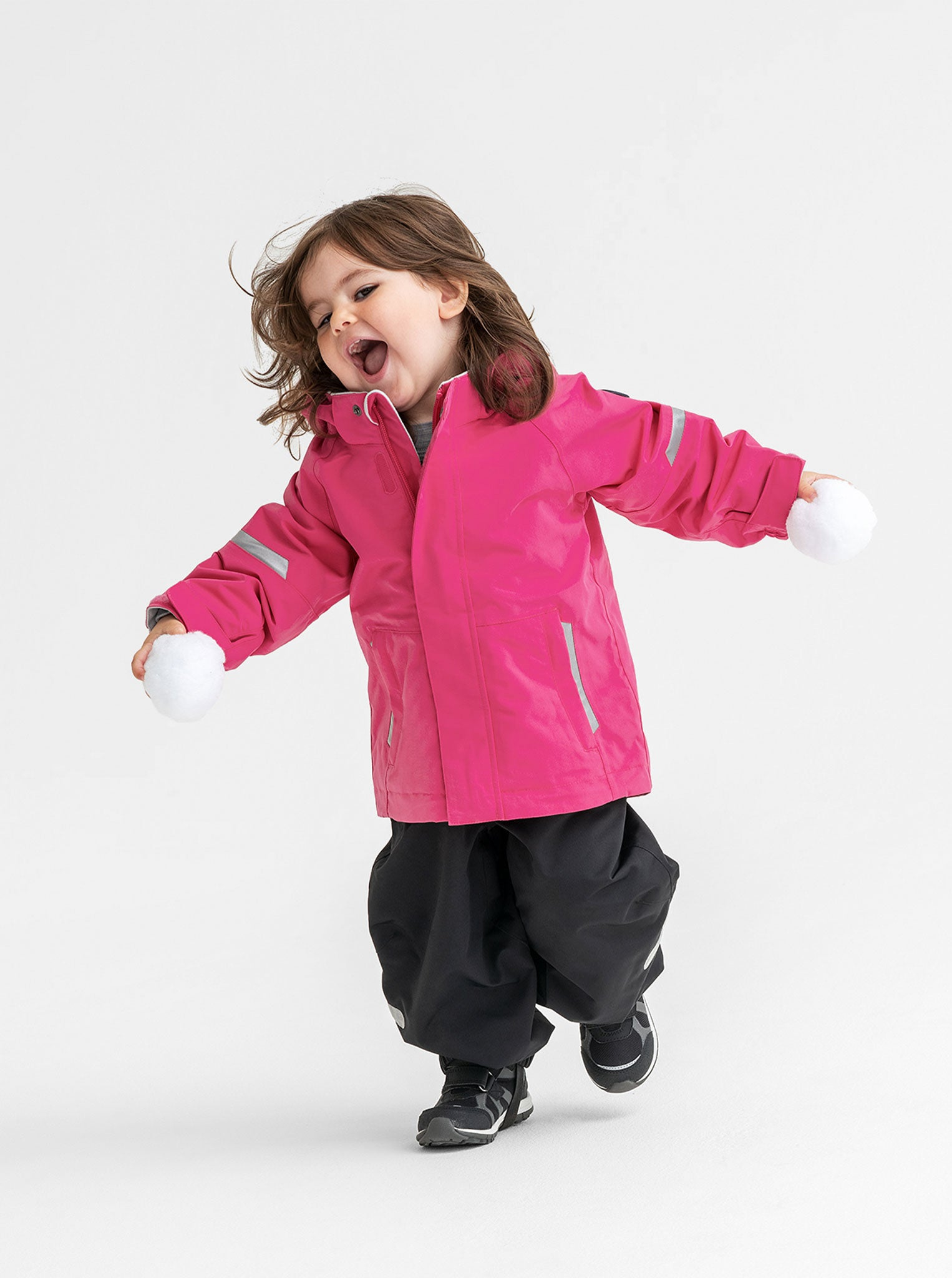 A young girl wearing a pink, toddlers waterproof jacket, paired with black, kids waterproof trousers, made of shell fabric.